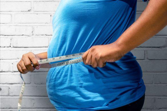 Otyły człowiek w niebieskiej koszulce mierzy obwód brzucha miarą krawiecką