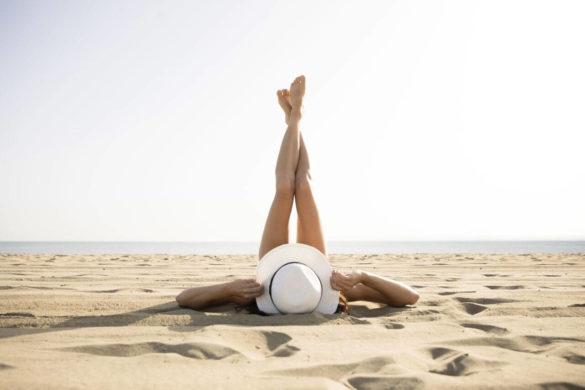 kobieta z kapeluszem na głowie opalająca się na piaszczystej plaży z nogami wyciągniętymi w górę
